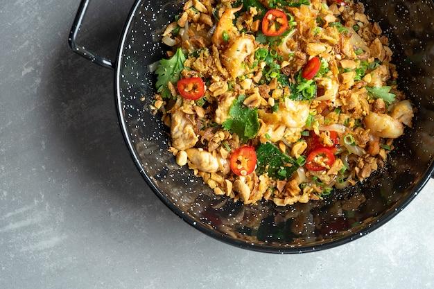 Bovenaanzicht op pad thai, of phad thai roergebakken rijstnoedel met groenten en kip, hete chili peper en peterselie in zwarte kom op grijze stenen oppervlak