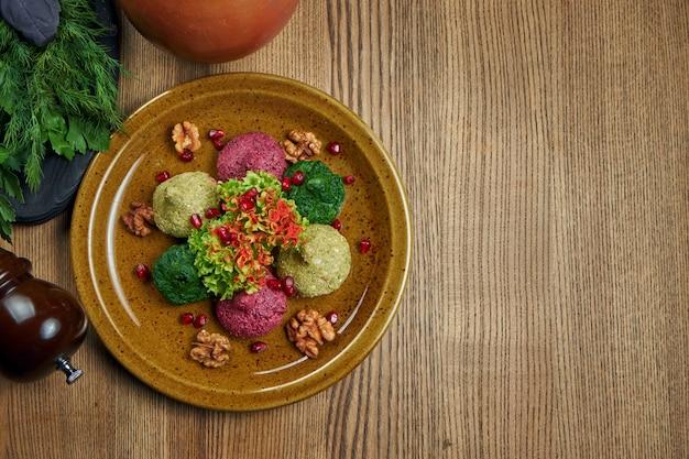 Bovenaanzicht op pkhali in keramische plaat. kopieer ruimte. traditioneel georgisch voorgerecht pkhali gemaakt van gehakte en gehakte kool, aubergine, spinazie, bonen, bieten en gecombineerd met walnoten, knoflook en kruiden