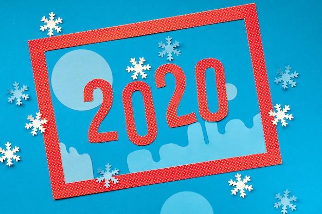 Bovenaanzicht op rood frame en nummer 2020 op abstracte winter achtergrond met sneeuwvlokken