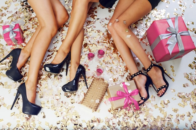 Bovenaanzicht op sexy vrouwen benen op achtergrond van glanzende gouden confetti, geschenkdozen, glazen champagne. tijd vieren.