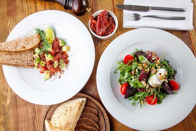 Bovenaanzicht op smakelijke groene salade met tomaat en bieten en runder (kalfs) tartaar met avocado en limoen. heerlijk diner. gezond eten. plat gelegd voedsel. uitzicht van boven
