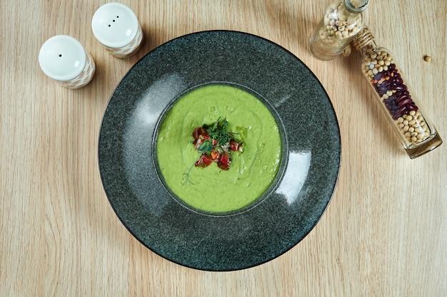 Bovenaanzicht op smakelijke koude groene avocado roomsoep met worstjes in een zwarte kom op houten tafel. dieet en vegetarisch eten.