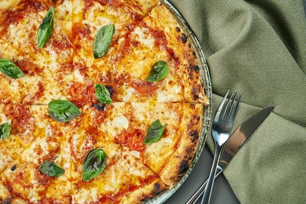 Bovenaanzicht op smakelijke pizza margherita met tomaten en basilicum op houten oppervlak in een restaurant. italiaanse keuken.