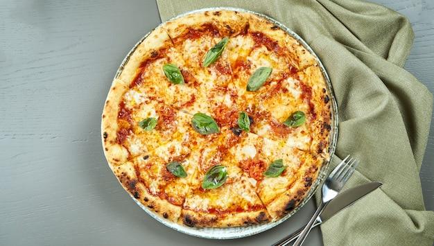 Bovenaanzicht op smakelijke pizza margherita met tomaten en basilicum op houten tafel in een restaurant. italiaanse keuken.