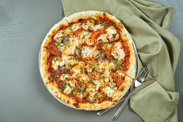 Bovenaanzicht op smakelijke pizza met rode saus, mosselen en garnalen op houten tafel in een restaurant. italiaanse keuken. pizza met zeevruchten