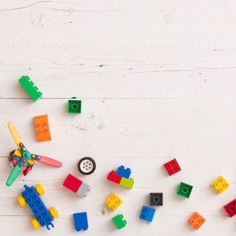 Bovenaanzicht op speelgoed, houten kubussen met cijfers en plastic bakstenen op witte houten achtergrond