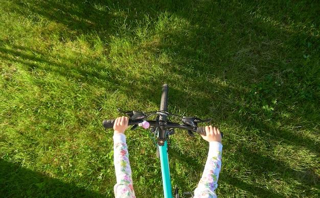 Bovenaanzicht op tiener meisje rijdt een fiets op helder groen gras