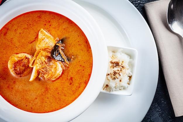 Bovenaanzicht op tom yum soep geserveerd in witte plaat met rijst