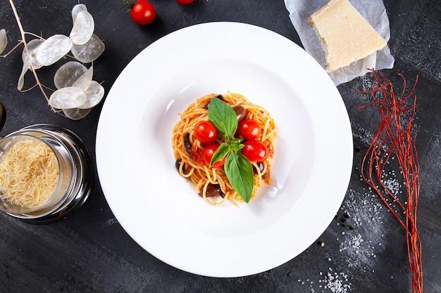 Bovenaanzicht op traditionele italiaanse pasta met basilicum en cherry tomaten in witte plaat. plat lag italiaanse keuken met kopie ruimte voor design. mediterrane noodle voor de lunch.