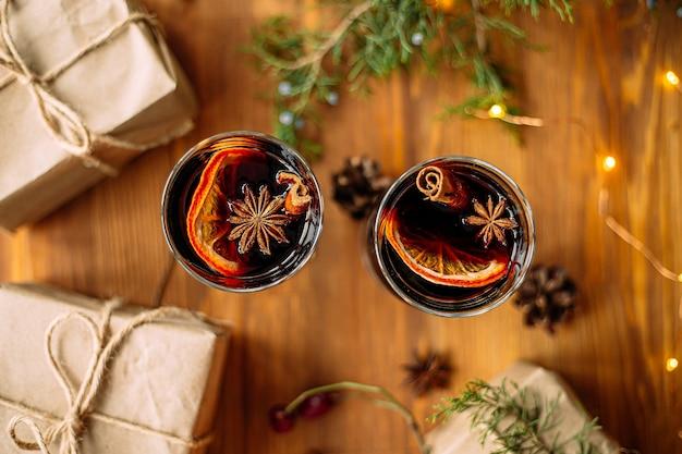 Bovenaanzicht op twee glazen mokken glintwine met ambachtelijke cadeautjes en guirlande lichten op de houten tafel