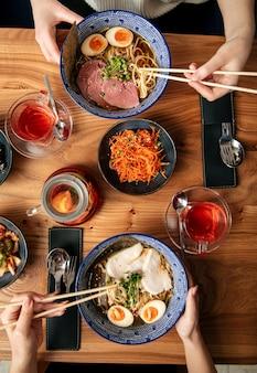 Bovenaanzicht op twee mensen eten japanse ramen noodlesoepen en andere aziatische gerechten