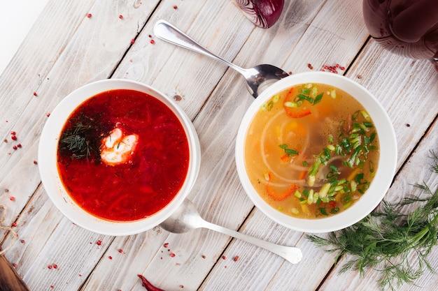 Bovenaanzicht op twee soepen borsch en groente op de lichte houten tafel