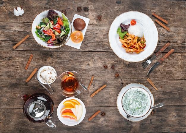 Bovenaanzicht op verschillende gerechten driegangenmenu op de houten tafel