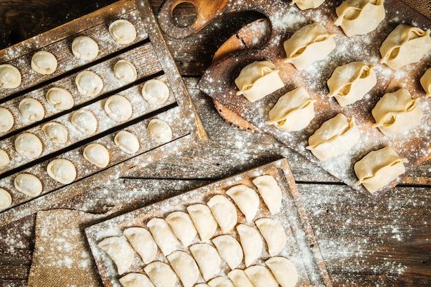 Bovenaanzicht op verschillende halffabrikaten dumplings op de houten planken met bloem