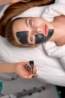 Bovenaanzicht op vrouw met zwart cosmetisch gezichtsmasker liggend op bed in de spa. gezichtspeelingmasker met houtskool, spa-schoonheidsbehandeling, huidverzorging. aantrekkelijke vrouwelijke cliënt krijgt procedures door professionals
