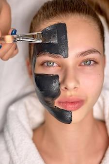 Bovenaanzicht op vrouw met zwart cosmetisch gezichtsmasker liggend op bed in de spa. gezichtspeelingmasker met houtskool, spa-schoonheidsbehandeling, huidverzorging. knappe vrouwelijke klant krijgt procedures door professionals