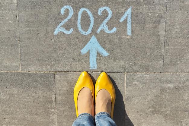 Bovenaanzicht op vrouwenbenen en tekst 2021 geschreven met krijt op grijze stoep