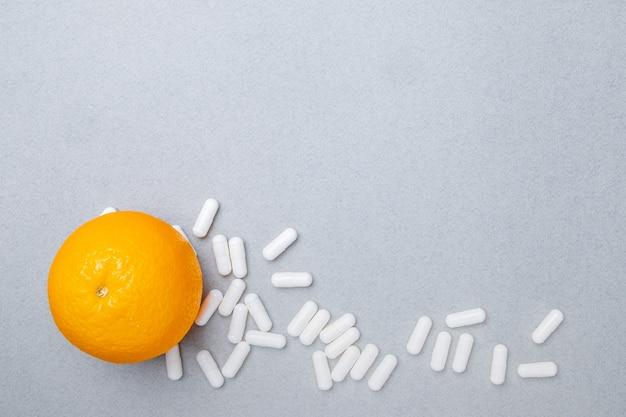 Bovenaanzicht op witte grote ovale pillen en rijpe sinaasappel op een grijze achtergrond