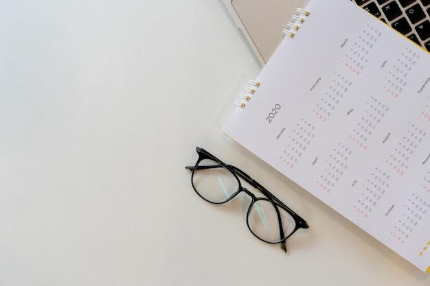 Bovenaanzicht op witte kalender 2020-schema met laptoptoetsenbord om afspraakvergadering te laten werken