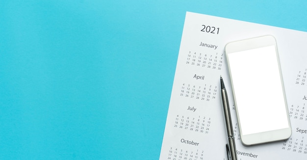 Bovenaanzicht op witte kalender 2021 schema met leeg scherm smartphone op blauwe kleur achtergrond