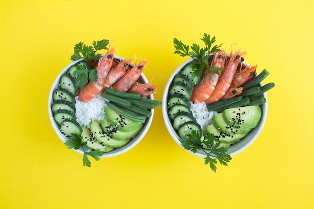 Bovenaanzicht op zaksalade met rode garnalen en groene groente in de witte kommen op de gele achtergrond