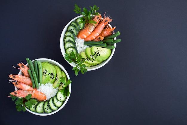Bovenaanzicht op zaksalade met rode garnalen en groene groente in de witte kommen op de zwarte achtergrond. ruimte kopiëren.
