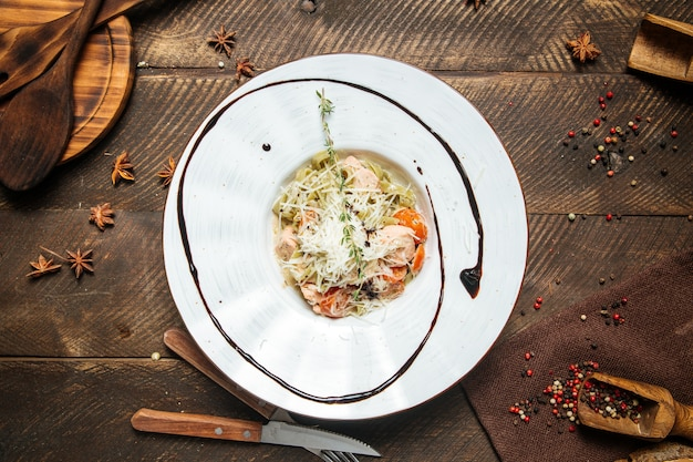 Bovenaanzicht op zalm tagliatelle met champignons op de houten tafel