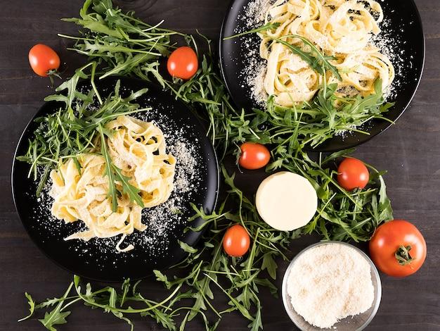 Bovenaanzicht op zelfgemaakte tagliatelle pasta met parmezaanse kaas, cherrytomaatjes en groen