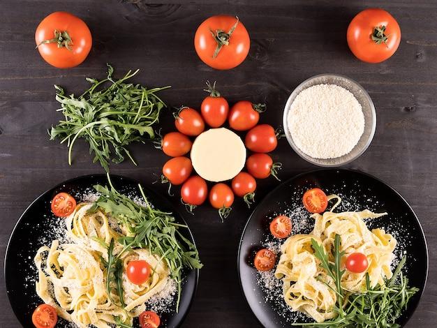 Bovenaanzicht op zwarte borden met pasta op een houten bord