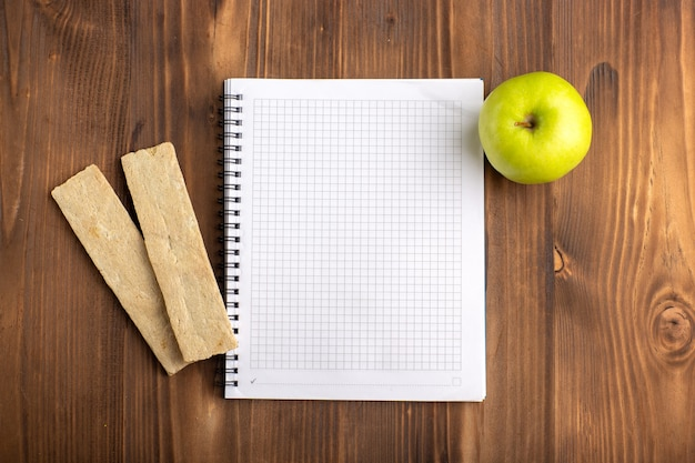 Bovenaanzicht open blauw voorbeeldenboek met crackers en groene appel op het bruine bureau