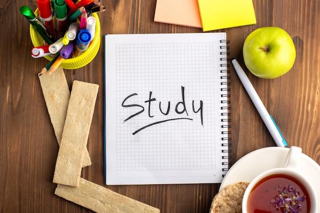 Bovenaanzicht open blauw voorbeeldenboek met crackers kopje thee en groene appel op het bruine bureau