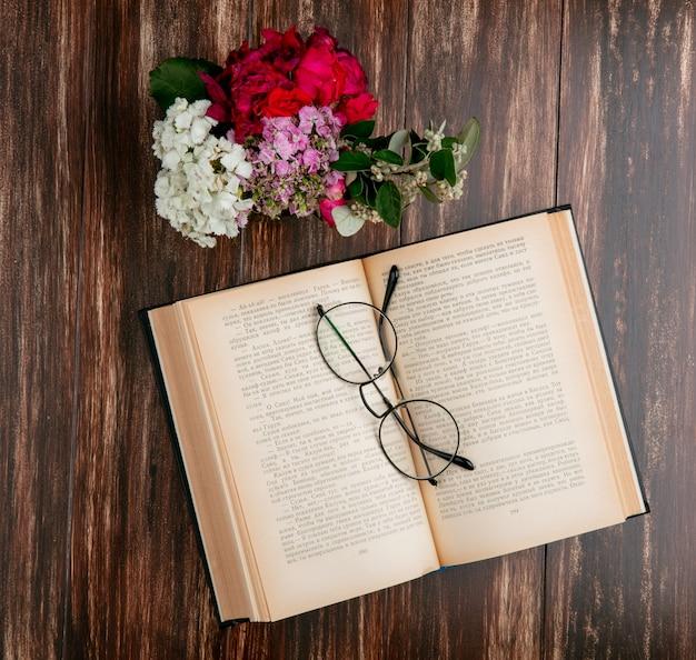 Bovenaanzicht open boek met optische glazen en bloemen op een houten achtergrond
