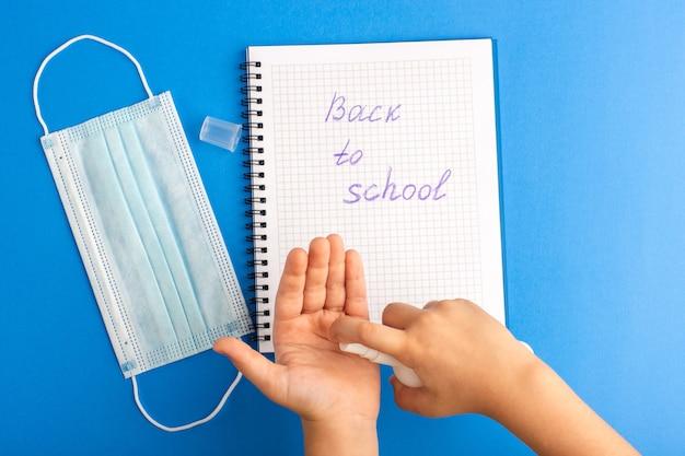Bovenaanzicht open voorbeeldenboek kind met behulp van spray op blauwe ondergrond