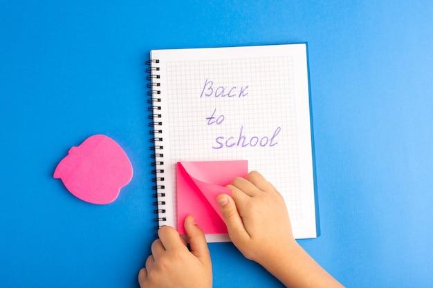 Bovenaanzicht open voorbeeldenboek kind met roze sticker op blauwe ondergrond