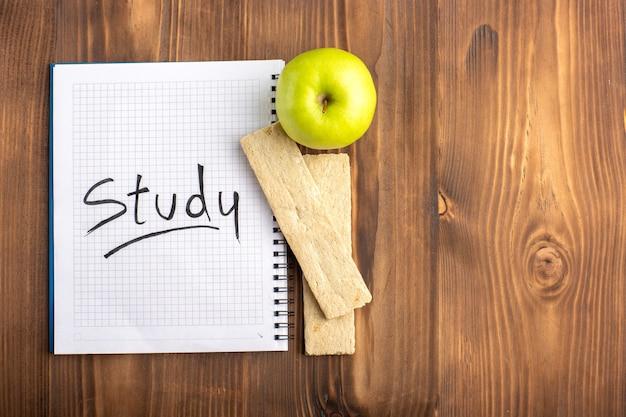 Bovenaanzicht open voorbeeldenboek met cracker en verse groene appel op het bruine bureau