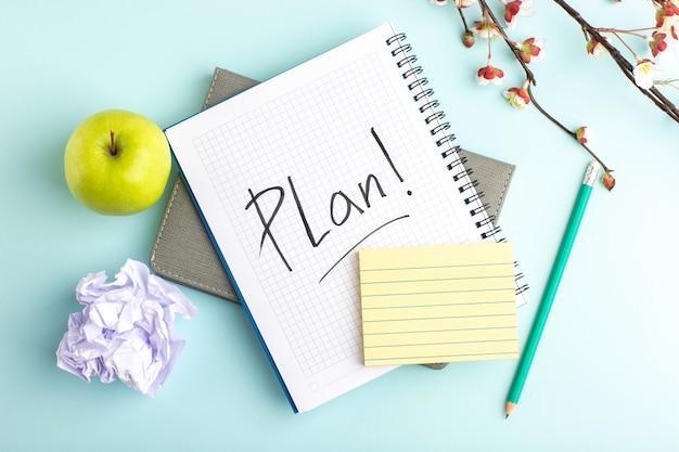 Bovenaanzicht open voorbeeldenboek met groene appel en bloemen op lichtblauw bureau