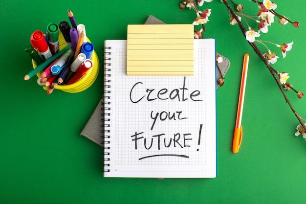 Bovenaanzicht open voorbeeldenboek met penbloemen en kleurrijke viltstiften op groen bureau