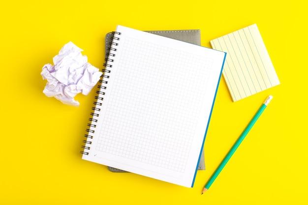 Bovenaanzicht open voorbeeldenboek met potlood op geel oppervlak