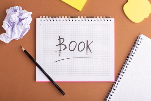 Bovenaanzicht open voorbeeldenboek met stickers en potlood op het bruine bureau