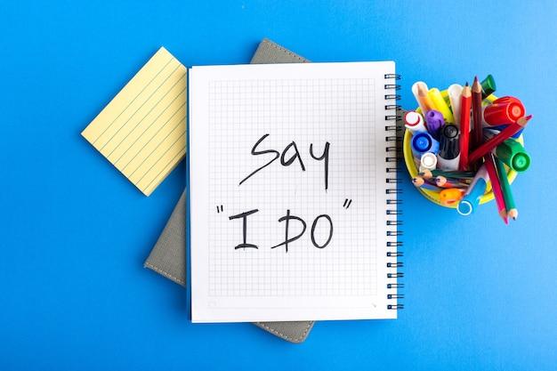 Bovenaanzicht open voorbeeldenboek met viltstiften en kleurrijke potloden op blauw bureau