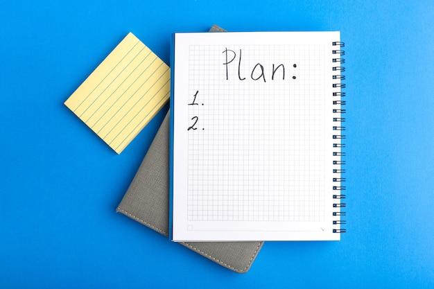 Bovenaanzicht open voorbeeldenboek op blauw bureau