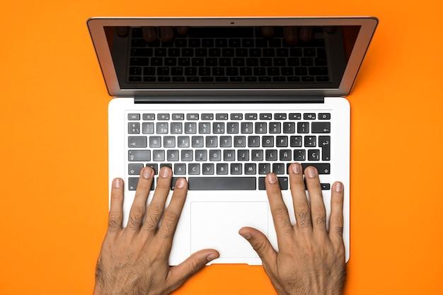 Bovenaanzicht opengeklapte laptop met oranje achtergrond