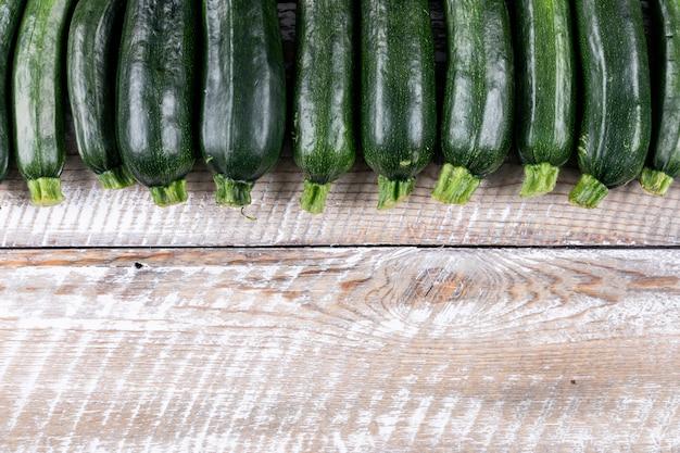 Bovenaanzicht opgesteld verse courgettes op lichte houten tafel.