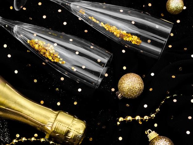 Bovenaanzicht opstelling van glazen gevuld met glitter voor nieuwjaarsfeest