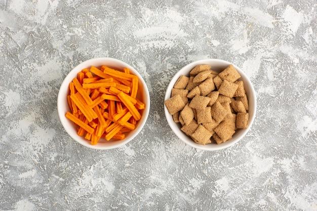 Bovenaanzicht oranje beschuit met kleine kussenkoekjes op wit bureau
