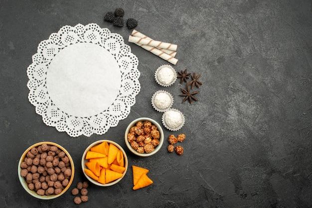 Bovenaanzicht oranje cips met zoete noten en vlokken op grijze oppervlakte snack maaltijd ontbijt noot