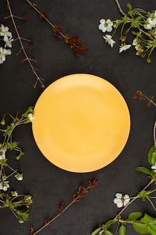 Bovenaanzicht oranje glasplaat rond witte bloemen op de donkere achtergrond
