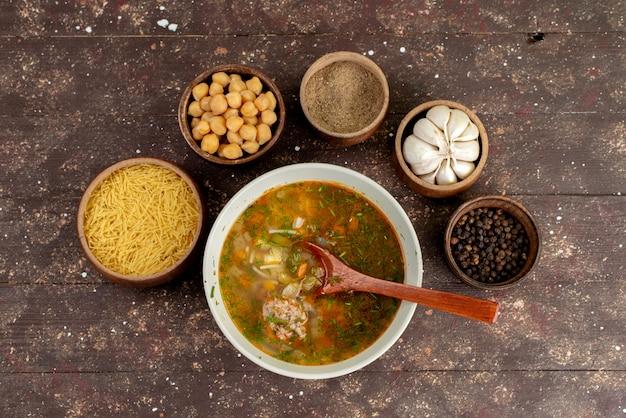 Bovenaanzicht oranje groentesoep met kruiden en knoflook op bruin, maaltijd soep brood