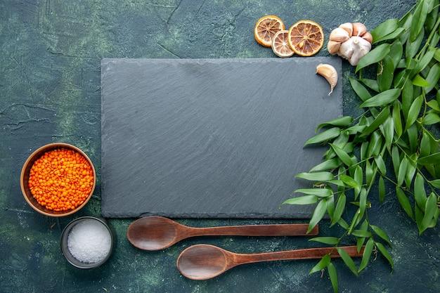 Bovenaanzicht oranje linzen met knoflook en zout op donkerblauwe achtergrond foto eten pittige hete peper kleur scherpe zaad soep
