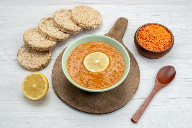 Bovenaanzicht oranje smakelijke soep met crackers citroen segment op wit, diner maaltijd soep